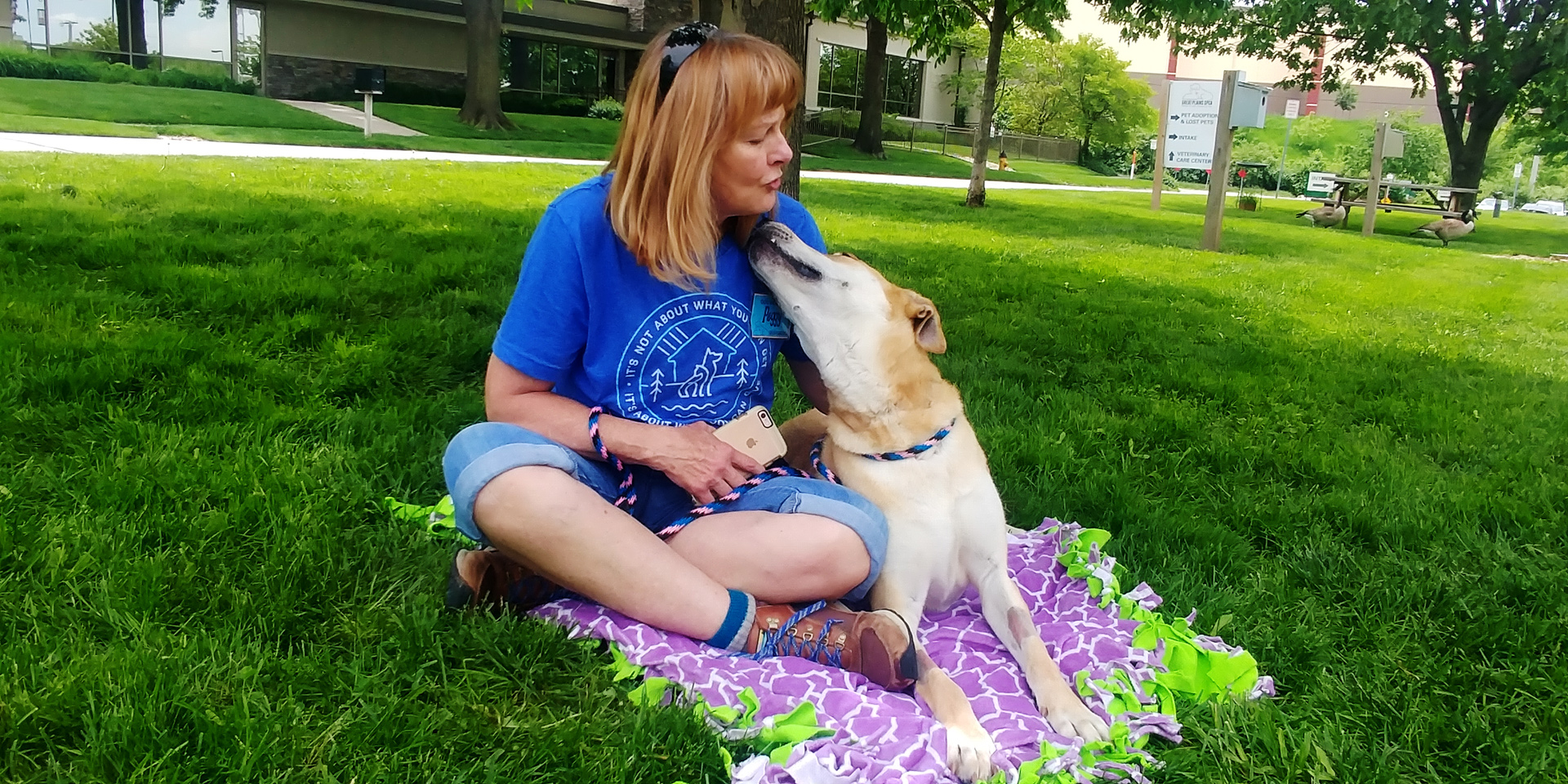 Woman sits on blanket with dog